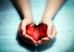 female-hands-holding-red-heart_blue-bg